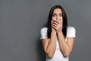 woman-on-grey-background-looking-shocked