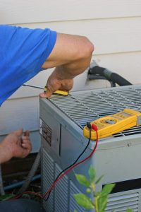 technician-hands-working-on-air-conditioner-outside-unit